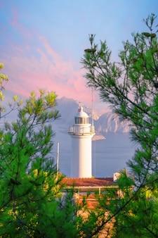 Faro de cabo gelidonia rodeado de pinos en el mar mediterráneo