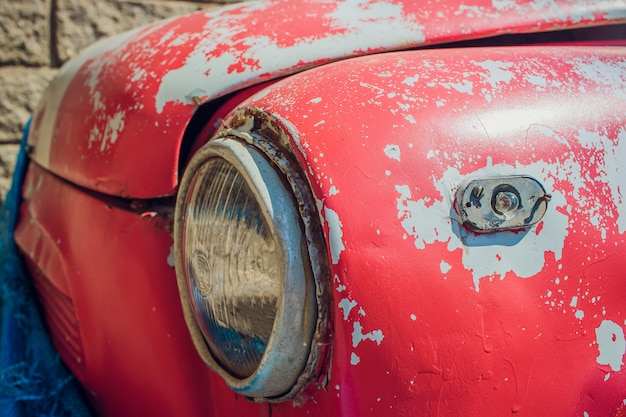 Faro delantero de un coche viejo en garaje.