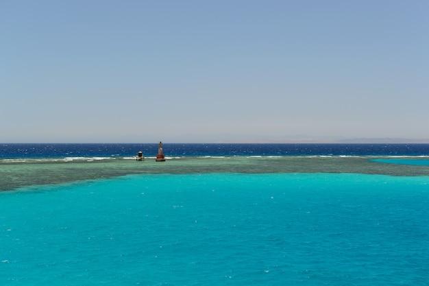 Faro en el horizonte del mar azul