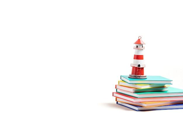 Faro de pie sobre la pila de libros. día internacional de la alfabetización, aventuras en libros, imaginación y concepto de viaje.