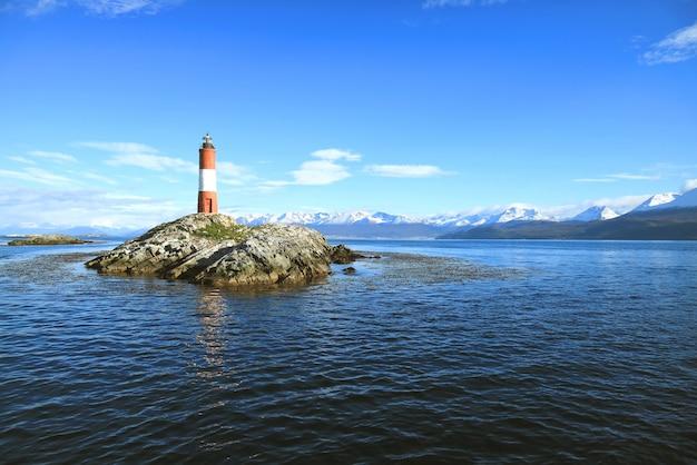 Faro rojo y blanco de les eclaireurs en islas rocosas del canal beagle, ushuaia, argentina