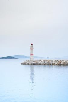 Faro solitario en un camino de piedra en medio del mar con vistas a las montañas y la niebla