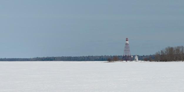 Faro y torre de vigilancia en la orilla del lago congelado, riverton, hecla grindstone provincial park, manit
