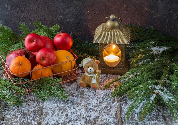 Farol viejo, un oso de juguete, nieve y una cesta de frutas