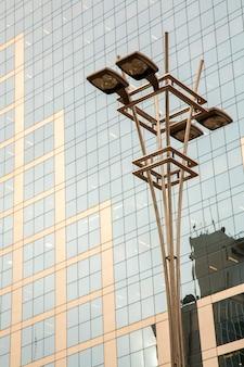 Farola delante de una fachada de vidrio y hormigón en un moderno edificio rascacielos corporativo