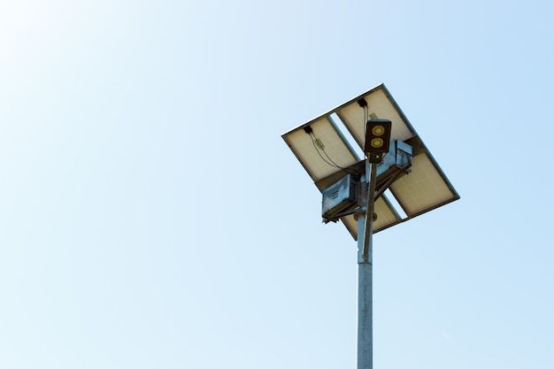 Farola con panel de células solares sobre fondo de cielo azul