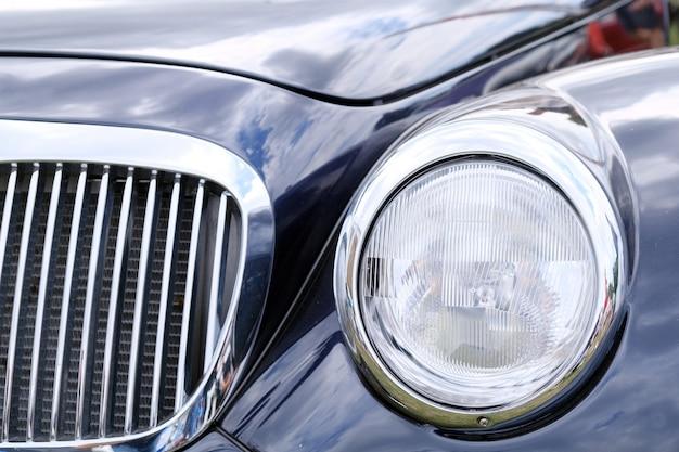 Faros, radiador y capó de lujo retro azul coche ckose-up.
