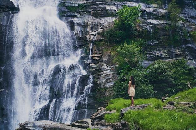 Fascinante disparo de ángulo bajo de una mujer admirando la cascada en el parque doi inthanon en tailandia