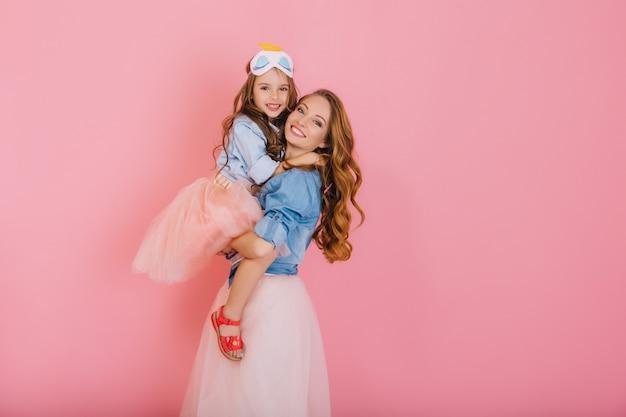 Fascinante madre rizada y hermosa hija de moda en el mismo atuendo posando juntas después de la fiesta de cumpleaños. retrato de niña linda en falda exuberante abraza a su hermana mayor con amor y sonrisa