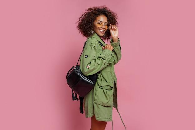 Fascinante modelo de raza mixta en chaqueta verde de moda posando sobre fondo rosa. gafas de sol amarillas, mochila negra.