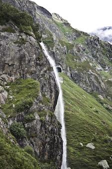 Fascinante paisaje de la hermosa cascada entre las montañas rocosas