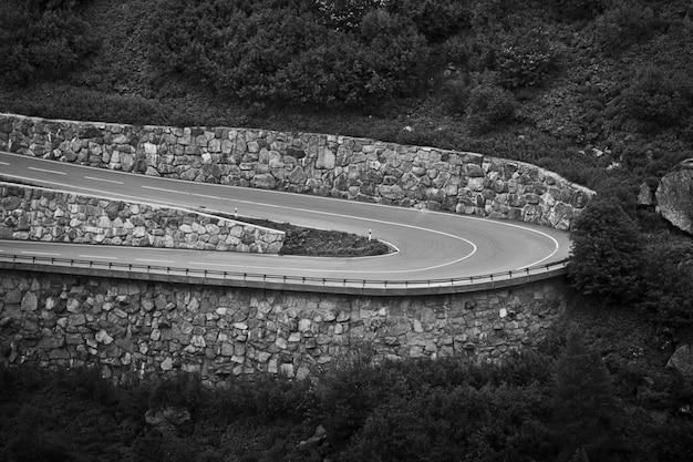 Fascinante toma en escala de grises de la carretera entre el hermoso paisaje