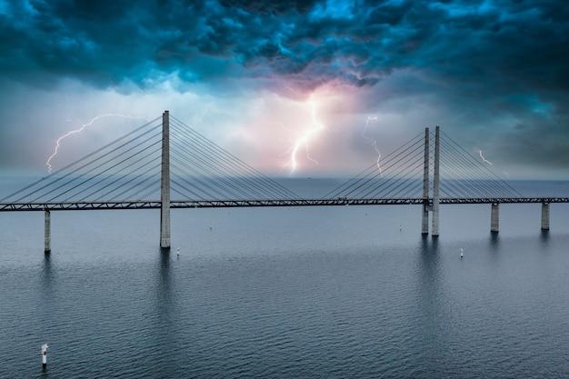 Fascinante vista aérea del puente entre dinamarca y suecia bajo el cielo con un rayo