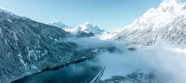 Fascinante vista de hermosos árboles cubiertos de nieve con un lago tranquilo bajo un cielo nublado