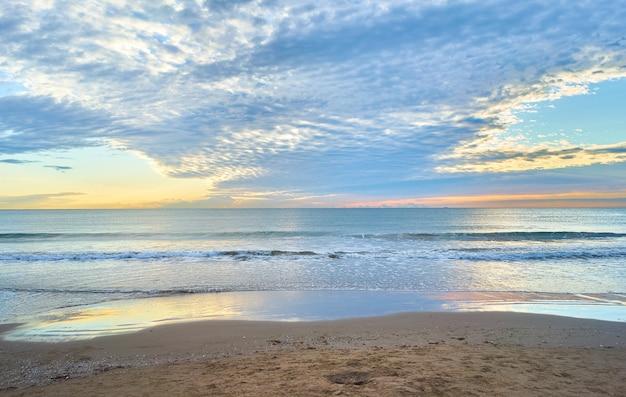 Fascinante vista del océano junto a la costa arenosa
