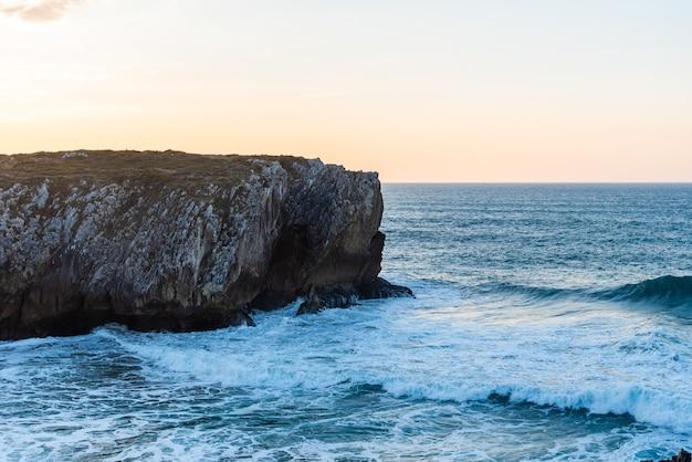Fascinante vista de las olas del océano rompiendo en las rocas cerca de la playa en un día claro