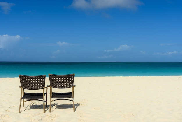 Fascinante vista de la playa y el mar, con dos sillas en la orilla
