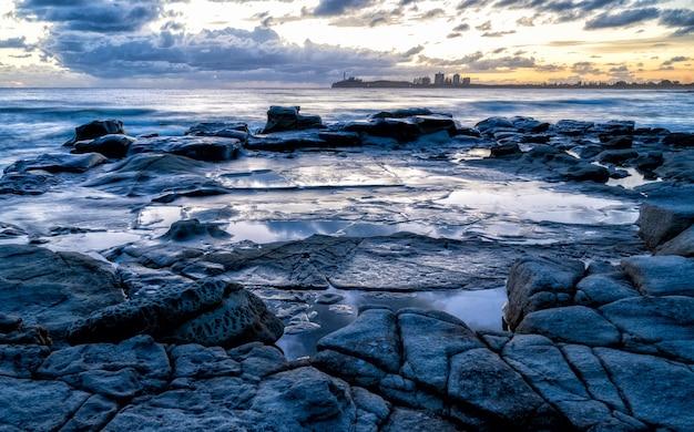 Fascinante vista de la puesta de sol sobre la costa rocosa en kap geinitzort en rostock, alemania