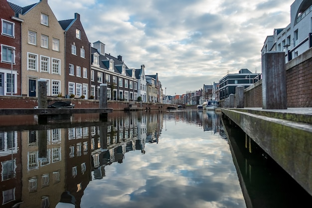 Fascinante vista del reflejo de los edificios en el río en un día nublado