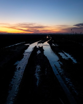 Fascinante vista del suelo helado en el campo durante la puesta de sol