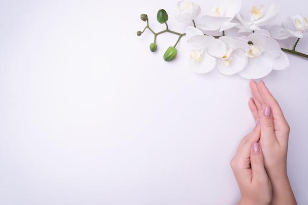 Fashionrt retrato mujer flores en la mano con un maquillaje contrastante brillante.