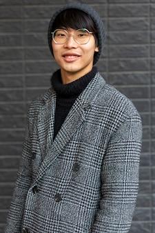 Fasionable atractivo hombre asiático vistiendo abrigo, sombrero, gafas sonriendo. ciudad urbana