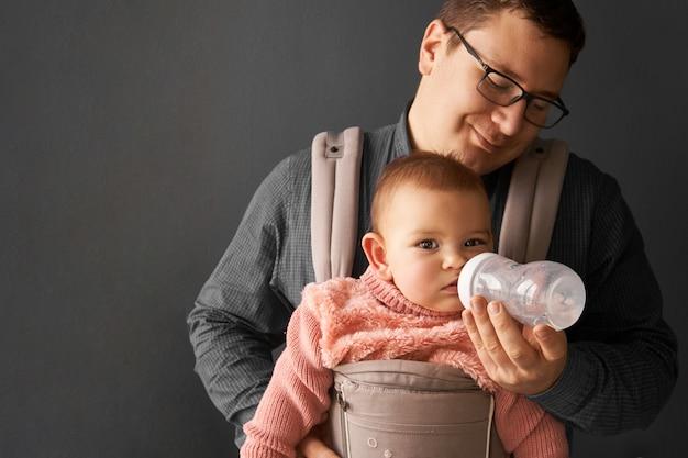 Fathre y su hijo en un portabebés en la pared de fondo gris, bebé vistiendo en la paternidad