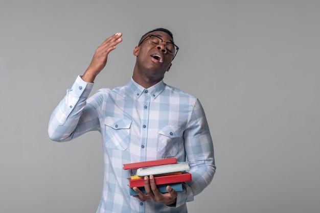 Fatiga. hombre afroamericano adulto joven con gafas con libros de pie cansado bostezando gesticulando con la mano