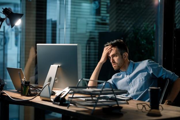 Fatiga hombre mirando la computadora en el trabajo