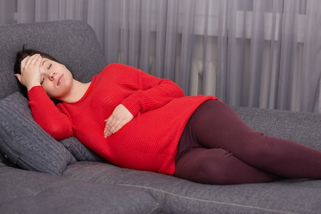 Fatiga la joven europea mantiene una mano sobre el estómago y otra sobre la frente, se acuesta en un cómodo sofá, descansa en casa, necesita descansar bien, sufre de dolor de cabeza.