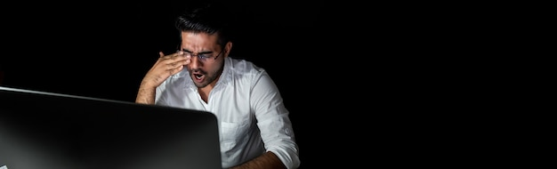 Fatigado empresario asiático sintiéndose adormilado y bostezando mientras trabajaba en el turno de noche