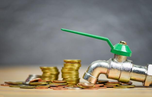 Faucet on money coin fondo de madera / ahorro de agua y caída de dinero faucet