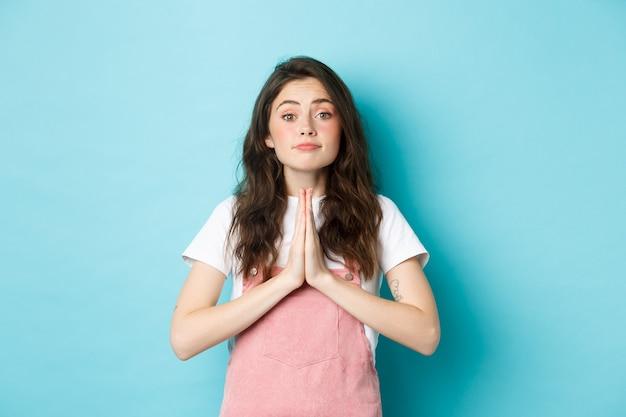 Por favor, ayúdame. linda mujer morena pidiendo un favor, tomados de la mano en oración, rogándole que compre algo, de pie contra el fondo azul.