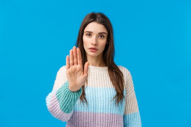 Por favor deje de. mujer atractiva joven asertiva y segura de aspecto serio que tira de la mano hacia adelante en prohibición, movimiento de desaprobación, muestra restricción diciendo suficiente, sin señal, de pie azul