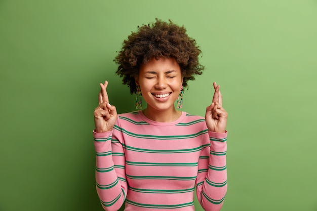 Por favor lo quiero. alegre joven afroamericana sonríe ampliamente vestida con un jersey de rayas casual cruza los dedos hace que el deseo ruegue a dios que el sueño se haga realidad aislado sobre una pared verde vivo