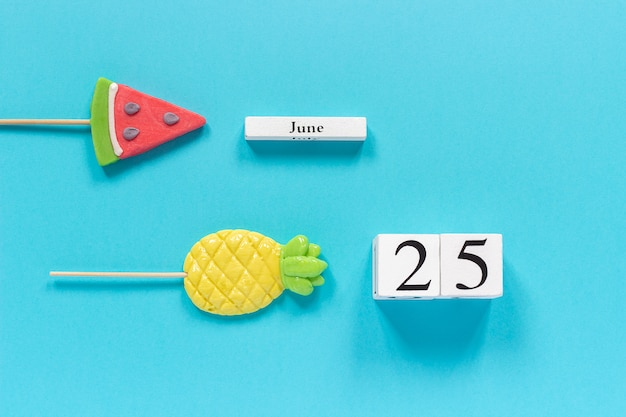 Fecha del calendario 25 de junio y frutas de verano piña dulce, paletas de sandía.