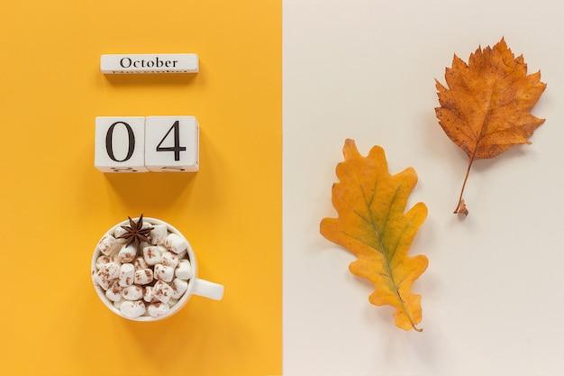 Fecha del calendario, taza de cacao con malvaviscos y hoja amarilla de otoño