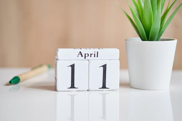 Fecha en cubos de madera blanca - el 11 de abril en una mesa blanca.