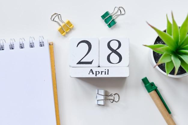 Fecha en cubos de madera blanca - el 28 de abril, 28 de abril en una mesa blanca. vista superior.