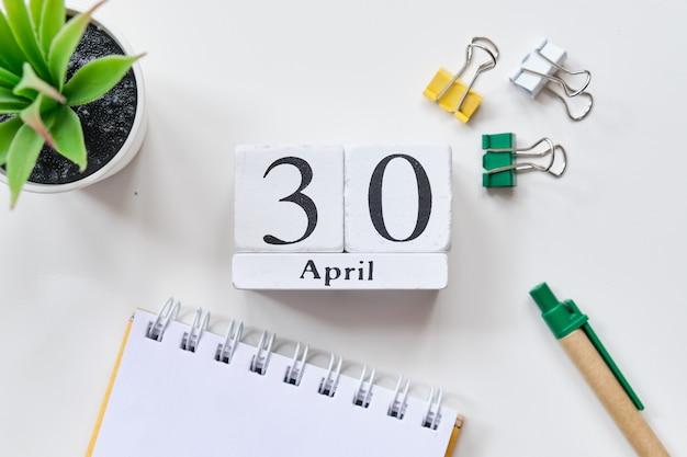 Fecha en cubos de madera blanca - el 30, 30 de abril en una mesa blanca. vista superior.