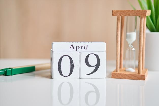 Fecha en cubos de madera blancos - el noveno, 09 de abril en una mesa blanca.