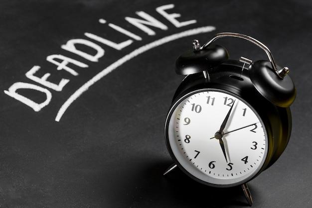 Fecha límite escrito en pizarra con reloj despertador