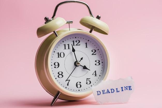 Fecha límite de texto en papel rasgado cerca del reloj amarillo sobre fondo rosa