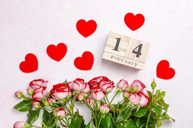 Fecha de san valentín con rosas y corazones rojos