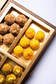 Fechas de bolas de avena o fruta seca laddu en un plato de embalaje de caja de regalo, enfoque selectivo