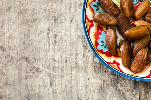 Fechas de comida en el plato en la mesa de madera copia espacio