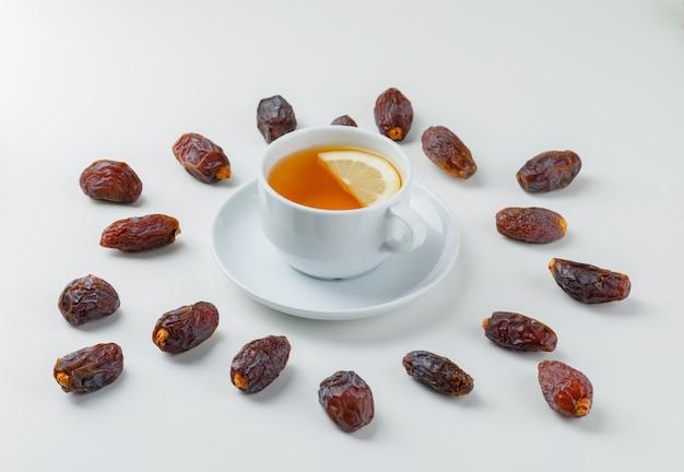 Fechas dispersas con una taza de té de limón.