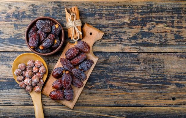Fechas frescas en un tazón y tabla de cortar con nueces en una cuchara de madera y palitos de canela vista superior sobre fondo de madera