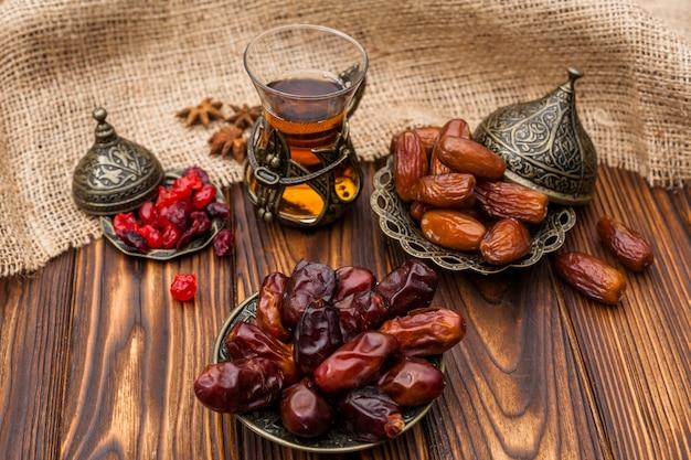 Fechas fruta en plato con vaso de té en mesa
