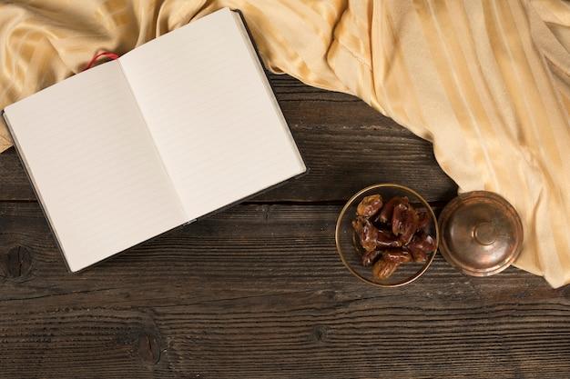 Fechas de frutas en un tazón con cuaderno en blanco